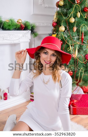 Beautiful woman in a red hat and a white dress. Christmas decor, sitting on a floor. - stock photo