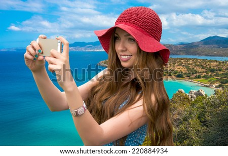 Beautiful woman in a red hat taken picture of herself, selfie. Sea coast in a quiet sunny day. Greece, Crete, Mirabello Bay, Aegean Sea - stock photo