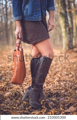 Beautiful woman in a romantic autumn fall scenery holding brown leather handbag. Fashion woman ready for shopping wearing sexy knee long boots  - stock photo