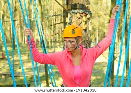 beautiful woman in a special outfit climbing the trees - stock photo