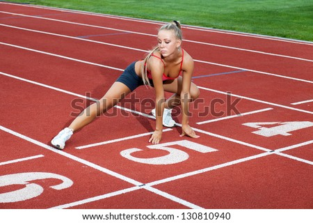 Beautiful woman in a sports suit doing training exercises before running