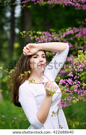 Beautiful woman in a spring garden under a blossoming tree - stock photo