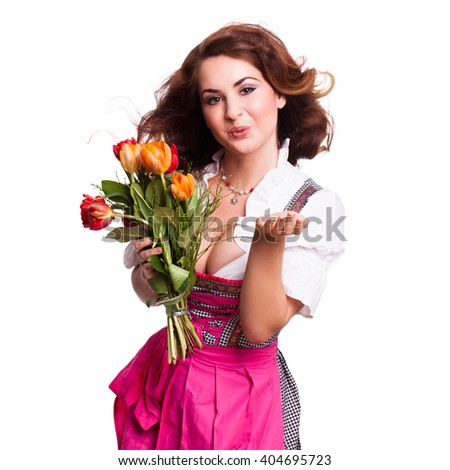 beautiful woman in a traditional bavarian dirndl with a bouquet of tulips isolated on white