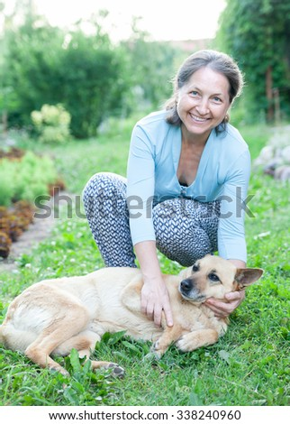 Beautiful woman in   age of   dog on   lawn.