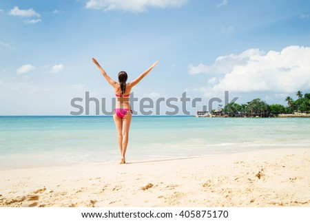 Beautiful woman in alluring pink bikini with hot legs and slim body posing on the beach with hands up.