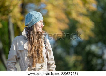 Beautiful woman in autumn park looking to the side, sideways. daylight, copy space