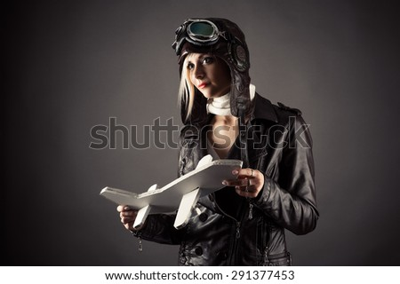 beautiful woman in aviator hat standing with toy airplane in hand