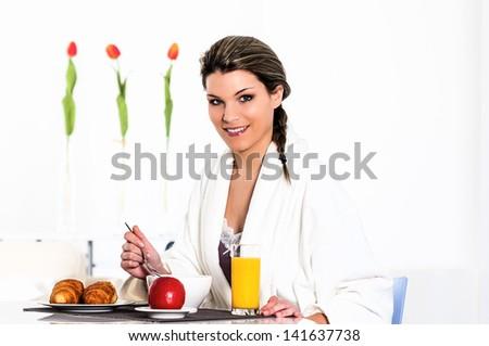 beautiful woman in bathrobe is having breakfast - stock photo