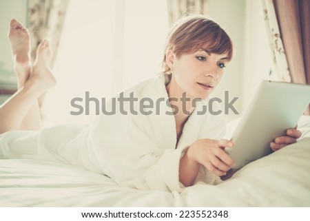 Beautiful woman in bathrobe lying on a bed with tablet pc - stock photo