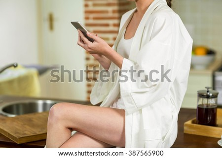 Beautiful woman in bathrobe sitting on worktop and typing a text message in kitchen - stock photo
