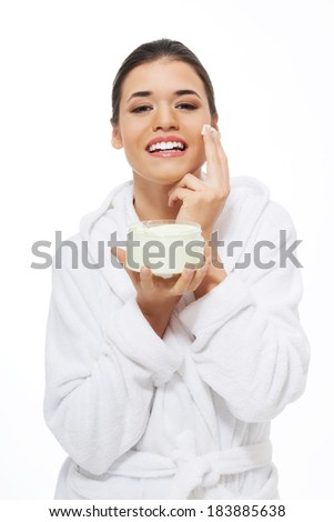 Beautiful woman in bathrobe with face cream. Isolated on white.