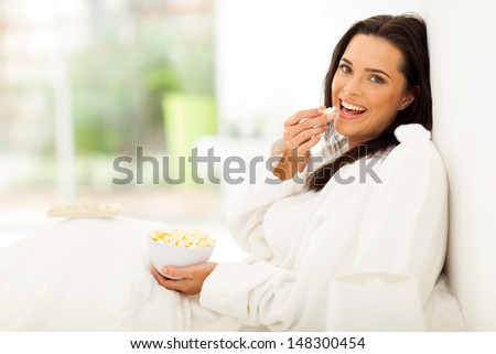 beautiful woman in bed eating popcorn and watching movie - stock photo