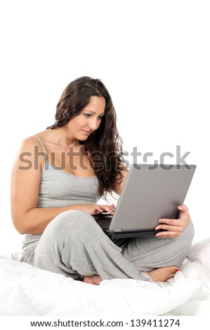 Beautiful woman in bed with laptop