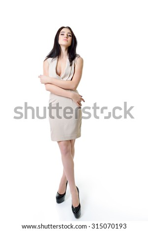 Beautiful woman in beige dress close up. Full length portrait.