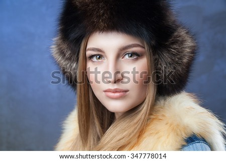 Beautiful woman in big black fur hat and vest over blue background  - stock photo