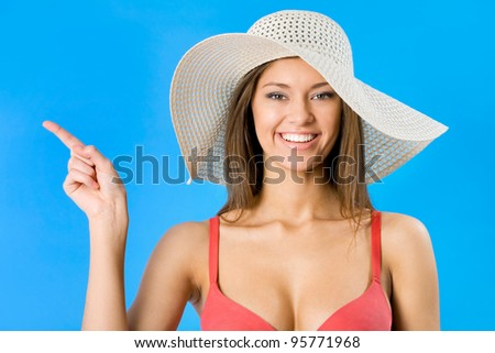 Beautiful woman in bikini and hat pointing on a blue background - stock photo