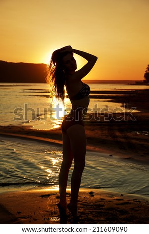 Beautiful woman in bikini on sunset background. Slim girl posing in a swimsuit. Female silhouette - stock photo