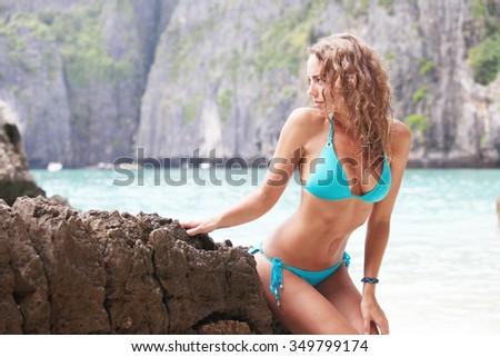 Beautiful woman in bikini posing in thai beach with rocks - stock photo