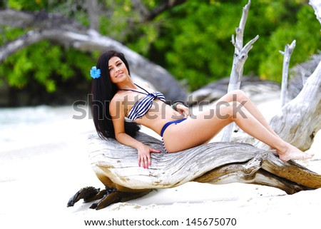 Beautiful woman in bikini posing on tropical beach - stock photo