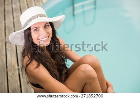 Beautiful woman in bikini relaxing by swimming pool - stock photo
