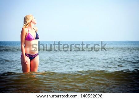 Beautiful woman in bikini sunbathing at the seaside blue sky - stock photo