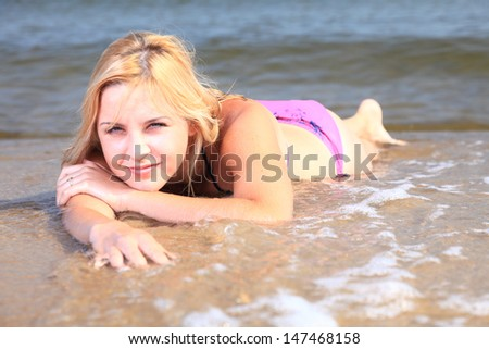 Beautiful woman in bikini sunbathing at the seaside blue sky - stock photo