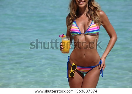 Beautiful woman in bikini with cocktail on beach - stock photo