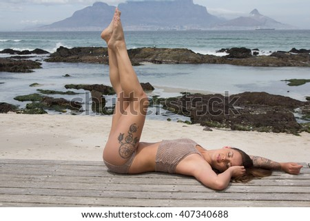 Beautiful woman in bikini with tattoos stretching her legs out while lying on the beach - stock photo