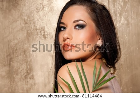 Beautiful woman in bikini with tropical leaf - stock photo