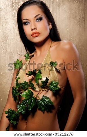 Beautiful woman in bikini with tropical leaves - stock photo