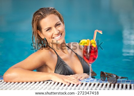 Beautiful woman in black bikini enjoying in sunbathing and relaxing in the swimming pool with red cocktail with lemon - stock photo