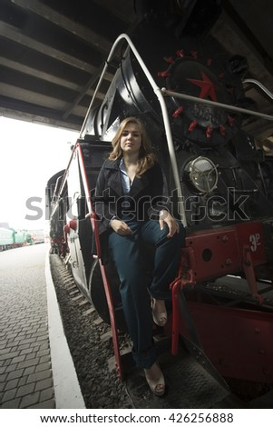 Beautiful woman in black coat posing on metal stairs of retro steam locomotive
