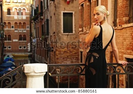 Beautiful woman in black dress on a bridge - stock photo