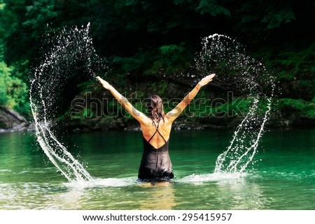 Beautiful woman in black dress playing with water in a river