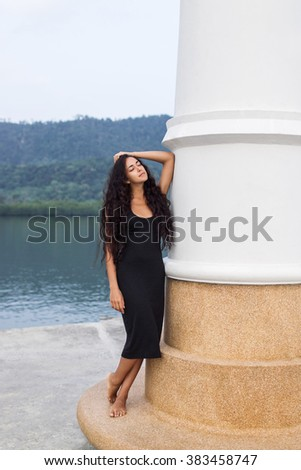 Beautiful woman in black dress with long black hair standing near white wall