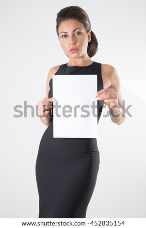 Beautiful Woman In Black Elegant Dress With Classic Hairstyle And Makeup Holding Blank Signboard Over White Background