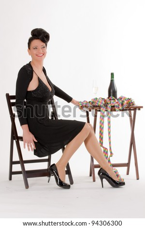 Beautiful woman in black evening dress waiting alone at a table on a man at a singles party /Dating party - stock photo