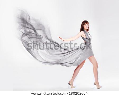 Beautiful woman in blowing Dress - stock photo