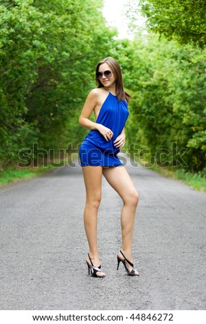 Beautiful woman in blue dress posing on the road - stock photo