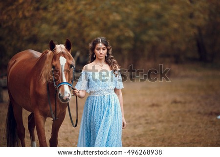 Beautiful woman in blue dress walking with his horse in the forest. Retro style.