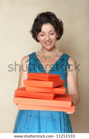 Beautiful woman in blue fashion dress holding a stack of red gift boxes ? smiling in her mid 30s