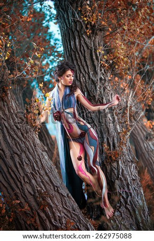Beautiful woman in bodyart on the autumn forest background - stock photo