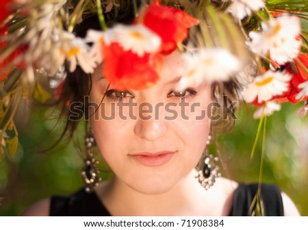 Beautiful woman in bright red poppy wreath, closeup