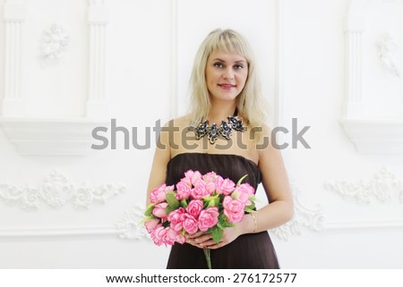 Beautiful woman in brown dress holds pink flowers
