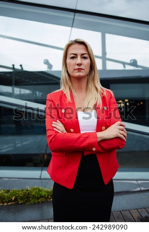 Beautiful woman in business suit looking at you with her arms folded confidently, business woman standing with crossed hand outside the office - stock photo