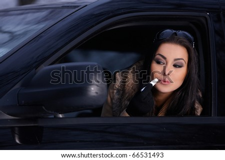Beautiful woman in car in snowy winter outdoors