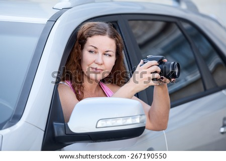 Beautiful woman in car window holding slr camera for photographing - stock photo