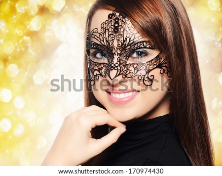 Beautiful woman in carnival mask over yellow background - stock photo