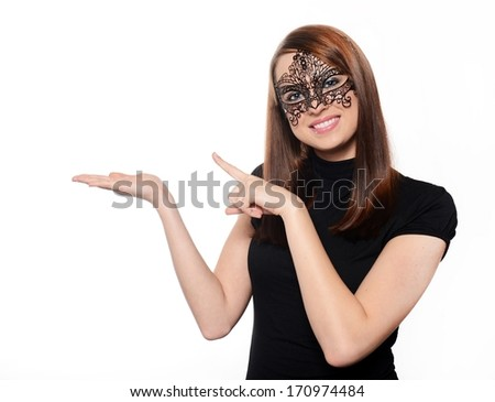 Beautiful woman in carnival mask pointing over white background - stock photo