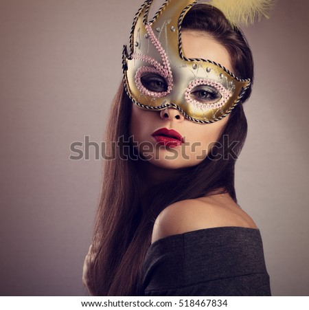 Beautiful woman in carnival mask with bright makeup and red lipstick. Closeup toned portrait